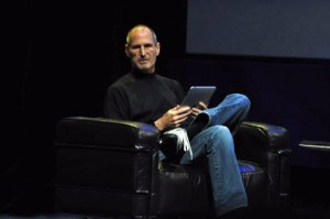 Steve Jobs sitting with an iPad